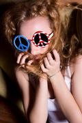Young girl with curly hair wearing sunglasses with the American - stock photo