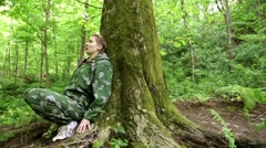 Girl shoots gun out of hiding. Accurate shooter. Woman shoots in the forest. - stock footage
