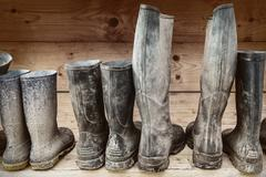 Row of muddy boots - stock photo