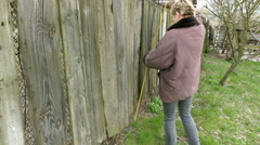 Country girl measures old fence with tape measure Stock Footage