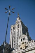 Palace of Culture and Science and street light against clear blue sky Stock Photos