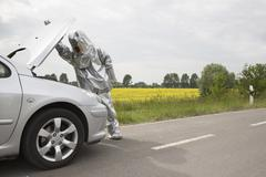 A person in a radiation protective suit looking under the hood of a car Stock Photos