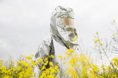 A person in a radiation protective suit standing in an oilseed rape field Stock Photos