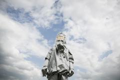 A person in a radiation protective suit standing against a cloudy sky Stock Photos