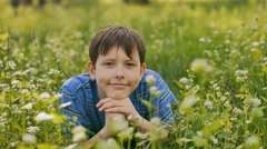 Boy teenager outdoors lying on green grass white flowers nature landscape Stock Footage