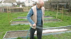 Senior elderly man waters a bed vegetable garden Stock Footage