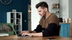 lucky handsome man working on a laptop, looking at camera and smiling. - stock footage