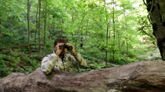 Man with binoculars in the woods. to seek, to hunt down. look for a solution. Stock Footage