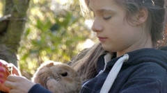 young girl and rabbit relax outside - stock footage