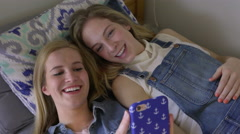 Best Friends Lay In Bed And Look At Smart Phone Together (Steadicam Shot) Stock Footage