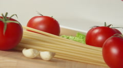 Spaghetti fall on a table between a ripe tomatoes - stock footage