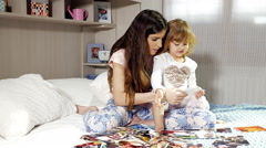 Young mother with daughter looking pictures of family on bed 4K Stock Footage