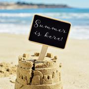 text summer is here in a signboard topping a sandcastle - stock photo