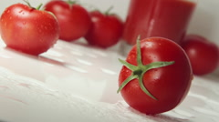 Ripe tomato rolls on a table near Fresh tomato juice Stock Footage