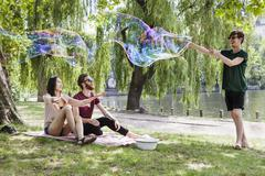 Happy friends enjoying with large bubble at park Stock Photos