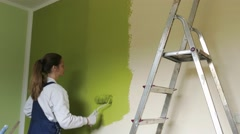 Housewife sweeps the walls with green paint Stock Footage