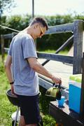 Young man pouring coffee from pot at park Stock Photos