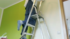 housewife sweeps the walls with green paint - stock footage