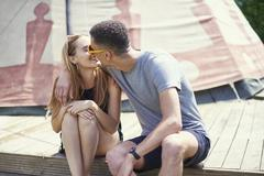 Young couple kissing on teepee structure while glamping Stock Photos