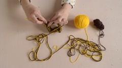 Woman crocheting yellow and brown yarn Stock Footage