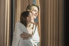 Affectionate young couple wrapped in sheet standing by window - stock photo