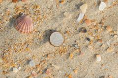 Rusty nickels lying on the sand on a sea beach - stock photo