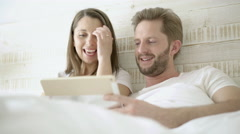 young couple with tablet in bed - stock footage