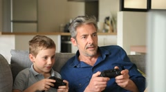 Father and son playing video game on tv - stock footage