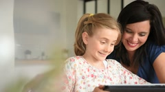 Mother with daughter using digital tablet - stock footage