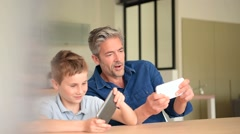 Man with young boy playing on smartphone - stock footage