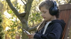 young girl relax and listen to music outside - stock footage