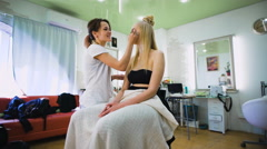 Beautiful top model in the beauty salon. Professional makeup artist making a - stock footage
