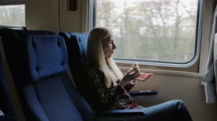 Young couple travel by train, eat sandwich and use tablet for browsing Stock Footage