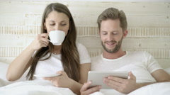 married young couple with coffee and ipad in bed - stock footage