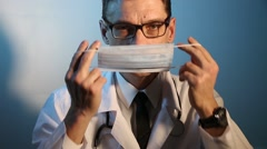 Adult male doctor wears a protective medical mask over his face Stock Footage