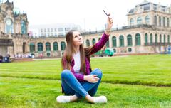 Woman tourist photographs the historic city center of Dresden, Germany - stock photo