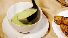 Broccoli cream soup being poured into the bowl with toasts aside - stock footage