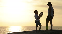 Mother and son stand on the cliff watching the sunset and start laughing Stock Footage