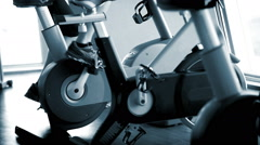 Man working out on the exercise bike at the hotel's gym blue sepia Stock Footage