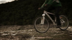 A young male on the bicycle riding to the mountain lake Stock Footage