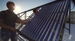 Men technicians assemble solar collector on the roof hurriedly sunset Stock Footage