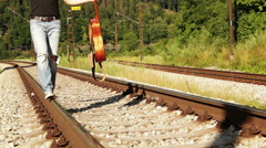 A teenager male walks along the railway with a guitar in his hands Stock Footage