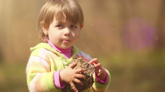 A little cute girl is fascinated with an old beehive (wasps' nest) she'd found Stock Footage