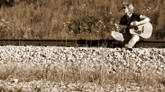 A left-handed long-haired guitarist sitting on the railroad and playing Stock Footage