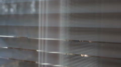 Woman looking through the blinds of the window to the street Stock Footage