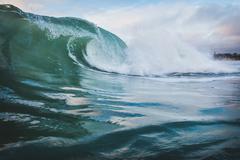 Surface level view of blue ocean wave rolling and splashing near coast, Encin Kuvituskuvat