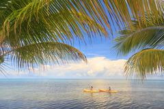Distant view of couple sea kayaking, St. Georges Caye, Belize, Central Americ - stock photo