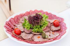 Served table layout with meat snack plate - stock photo