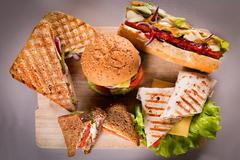 Fast food plate with burger hot dog sandwiches chicken wrap - stock photo