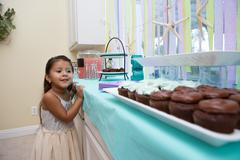Young girl looking longingly at cakes on kitchen work surface Stock Photos
